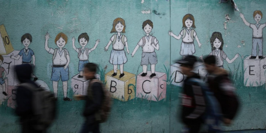 Palestinian children walk past a mural on their way to a UN-run school in Gaza City on 14 December (AFP)